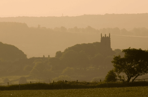 overlooking a church and fields in a spring mist